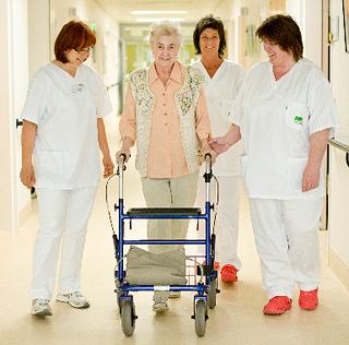 Drei Schwestern laufen mit einer Patientin mit Gehhilfe auf dem Krankenhausflur