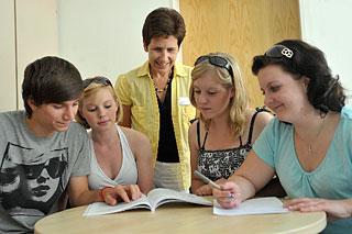 Schülerinnen und Schüler beugen sich mit der Dozentin über ein Lehrbuch