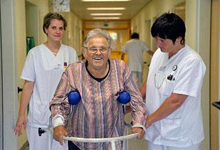 Patientin gestützt von zwei Schwestern beim gehen auf dem Krankenhausgang
