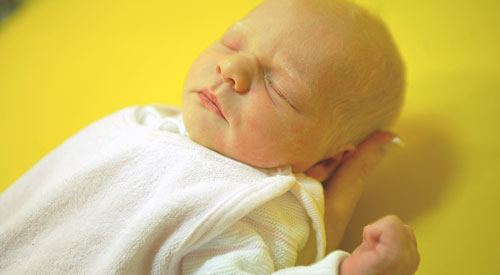 Neugeborenes wird von einer Hand getragen
