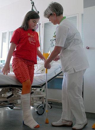 Mädchen mit Gipsbein steht an ihrem Bett. Schwester hilft beim Gehen