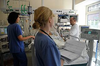 Zwei Pflegerinnen mit Arzt inmitten von intensivmedizinischen Geräten