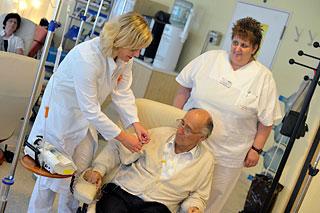 Zwei Krankenschwestern kümmern sich um älteren Herrn