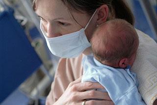 Intensivschwester mit Mundschutz hält ein Frühgeborenes auf dem Arm