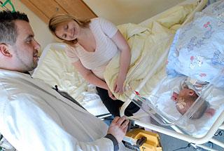 Oberarzt Stangl am Bettchen eines Neugeborenen, die Mutter sitzt daneben