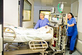 Intensivstation: Zwei Schwestern schieben ein Patientenbett mit Geräten