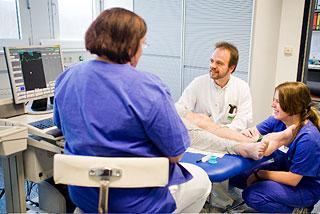 Diagnostik: Facharzt und zwei Schwestern sitzen um einen Patienten herum
