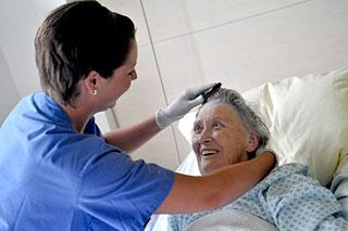 Pflegerin kämmt Patientin die Haare