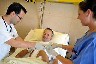 Arzt und Pflegerin legen einem Patienten den Verband an