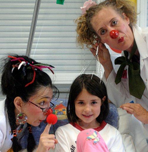 Zwei Clowninnen machen Späßchen mit einer jungen Patientin