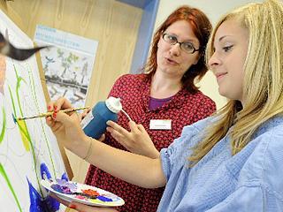 Therapeutin und Patientin beim Malen an einer Staffelei