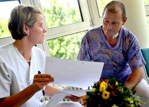 Pflegerin zeigt Patient etwas in einem Dokument