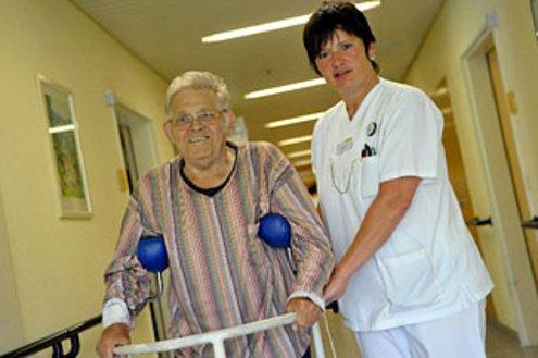 Pflegerin stützt Patienten beim Laufen
