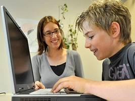 Therapeutin mit einem Jungen am Laptop